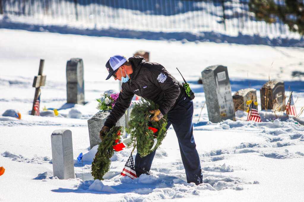 Eagle River Fire Protection's Tyler Watkins lays wreaths for veterans during the Wreaths Across America Saturday in Minturn. The local 10th Mountain Chapter of the National Society of Daughters of the American Revolution organized the local event, hoping it would become an annual event. | Chris Dillmann/cdillmann@vaildaily.com
