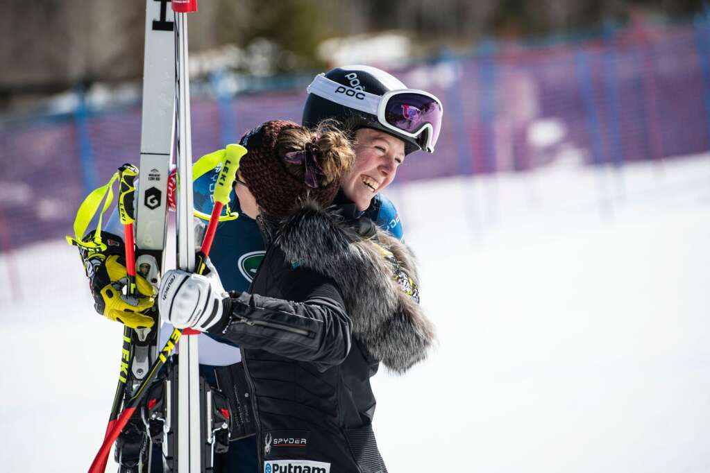 American alpine skier AJ Hurt, left, congratulates Laurenne Ross after they both got on the podium for the Women's Downhill National Championship at Aspen Highlands on Saturday, April 10, 2021. Ross will be retiring this week and took home the gold medal. (Kelsey Brunner/The Aspen Times)