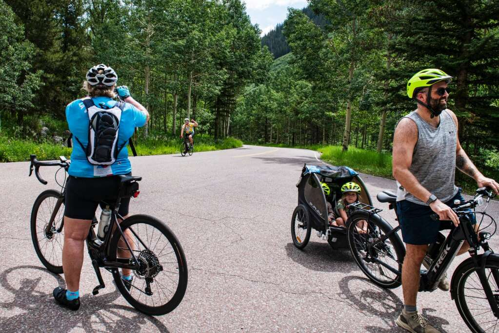 E-bikers stand at the top of Maroon Creek Road to turn into the parking lot for the Maroon Bells day use area in Aspen on Thursday, July 22, 2021. (Kelsey Brunner/The Aspen Times)
