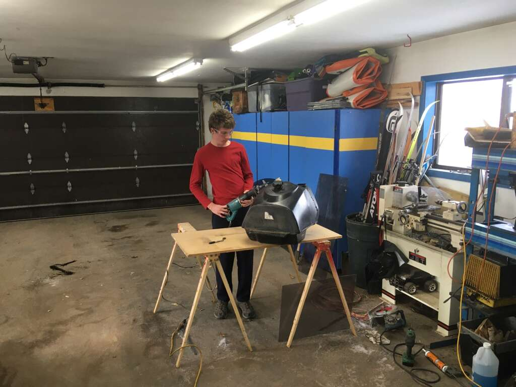 Connor Hoffman cuts open the gas tank from an old snowmobile so he and his father, Greg, can use it for battery storage on their electric snowmobile project.