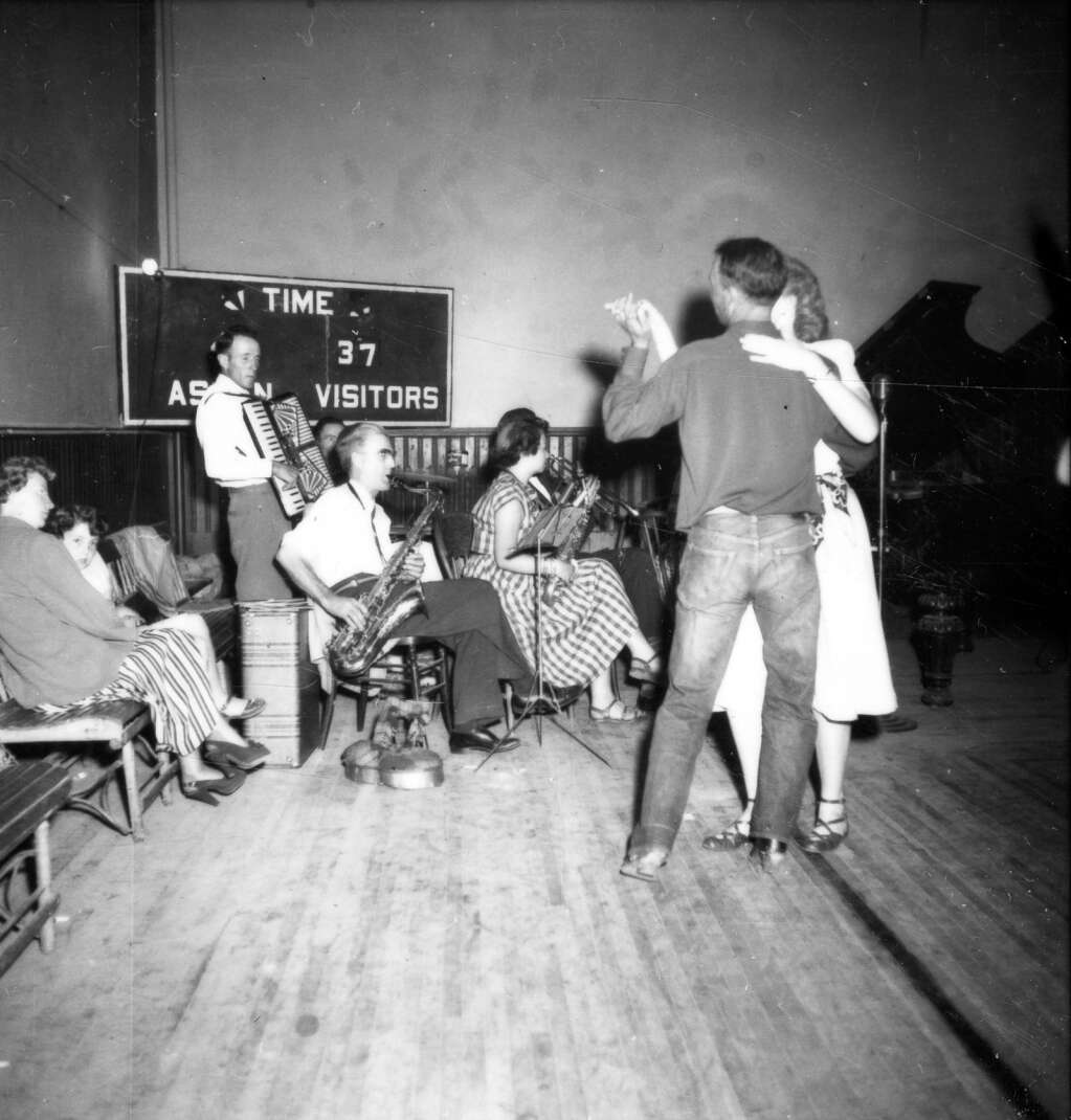 One b/w photograph of a cowboy dance held in the Armory Hall (City Hall) in Aspen on August 14, 1949.  There is a couple dancing in front of a band that is sitting in the corner playing. Aspen Historical Society, Berko Collection