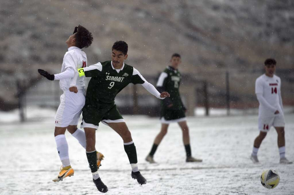 Summit High Tiger Ivan Gallardo Gutierrez vies for a head ball against a Glenwood Springs Demon player during a snowy Senior Day match at Climax Molybdenum Field at Tiger Stadium on April 15, 2021. The Tigers beat the Demons 4-0.