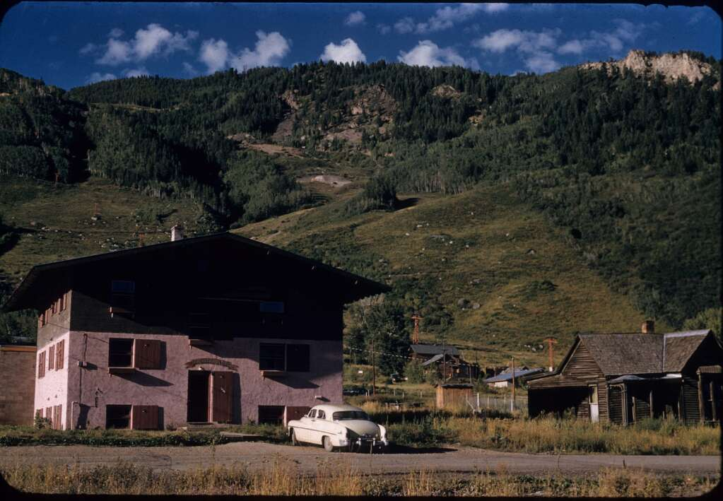 The Mountain Chalet Ski Lodge, seen here in the late summer or fall of 1955, stands alone with some old wooden cabins to the right. | Courtesy Aspen Historical Society, LeMassena Collection