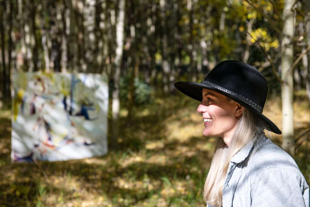 Artist Kaitlyn Tucek stands in an aspen grove with one of her paintings for her temporary exhibition, 'The Lilac Hour' on display for two days in Ashcroft Ghost Town on Friday, Sept. 17, 2021. (Kelsey Brunner/The Aspen Times)