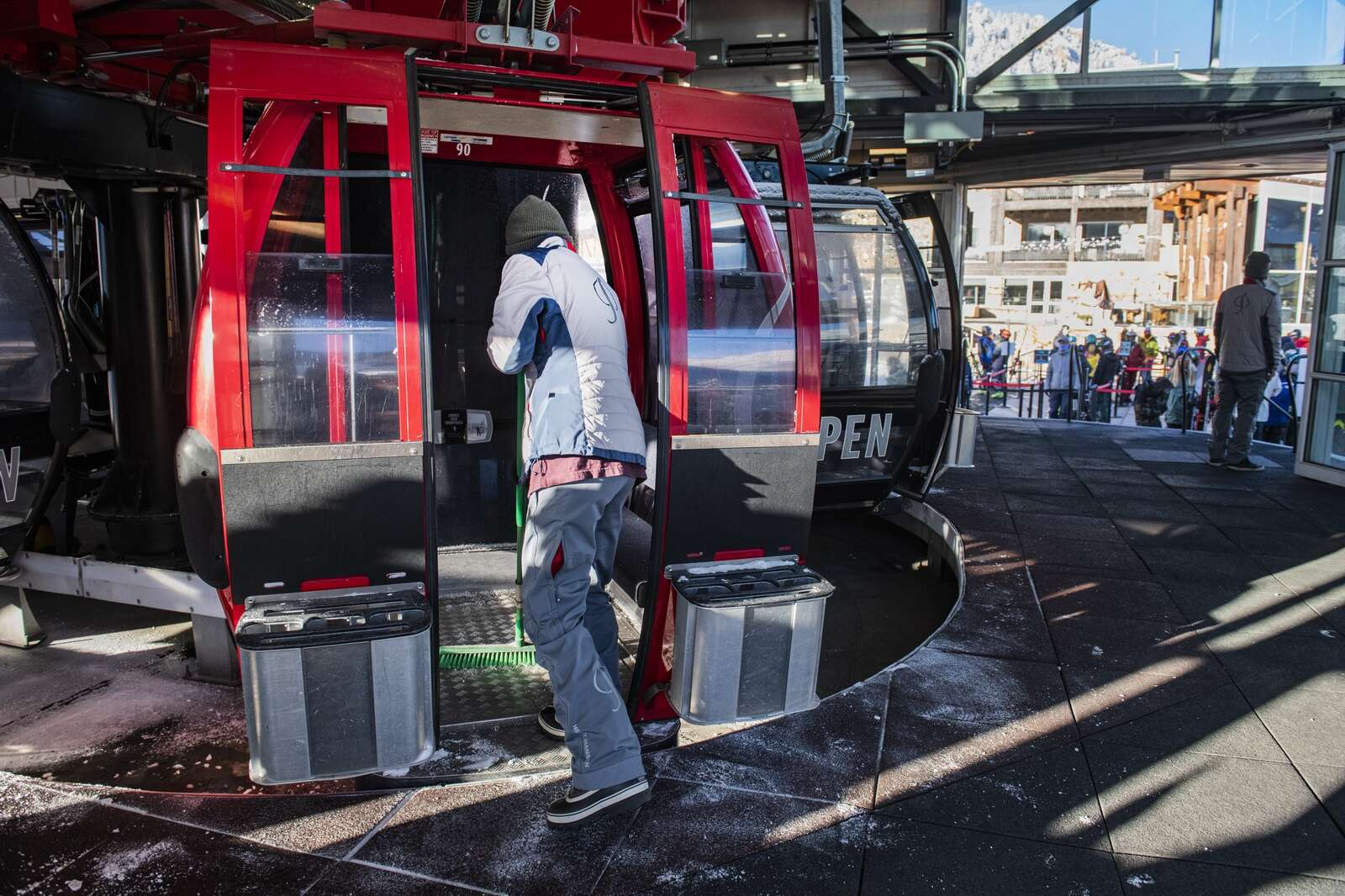 An Aspen Skiing Company employee sweeps snow out of one of the cars on the Silver Queen Gondola as people line up for opening day on Aspen Mountain on Wednesday, Nov. 25, 2020. (Kelsey Brunner/The Aspen Times)