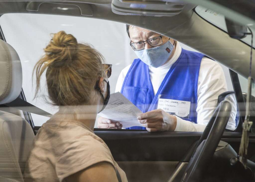 Emil Chuang, MD, right, speaks with a patient to confirm her appointment for a Moderna vaccination at the Utah Film Studios. | Tanzi Propst/Park Record