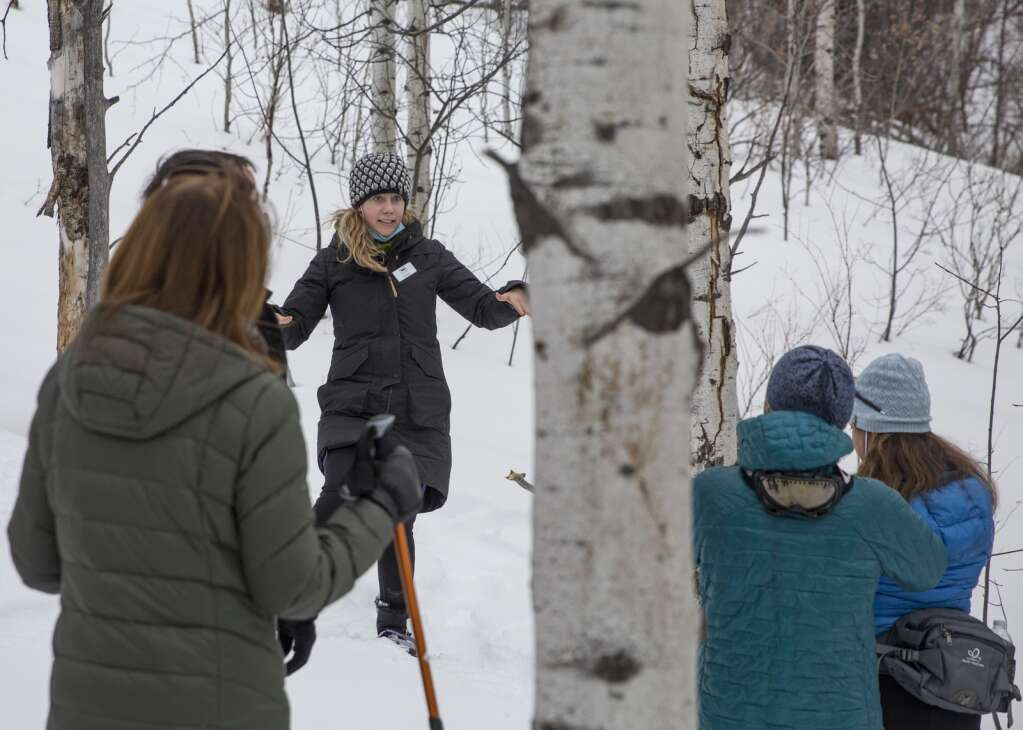 Minda Stockdale, center, speaks to a group of snowshoers along the McPolin Farm Trail, sharing history of the area and of the McPolin farm. (Tanzi Propst/Park Record)