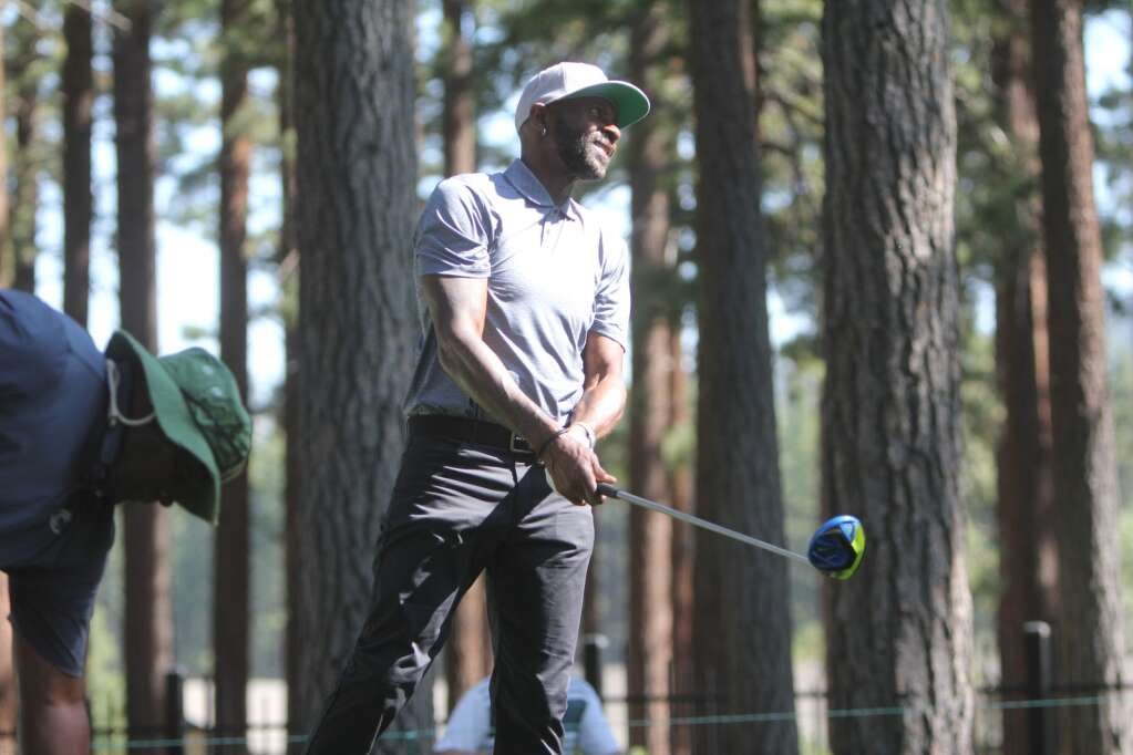 Jerry Rice uses body language to guide a tee shot.